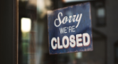 """A black """"Sorry, We're Closed"""" sign behind a glass door"""
