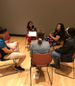 5 students sit in a circle in deep discussion around identity and culture